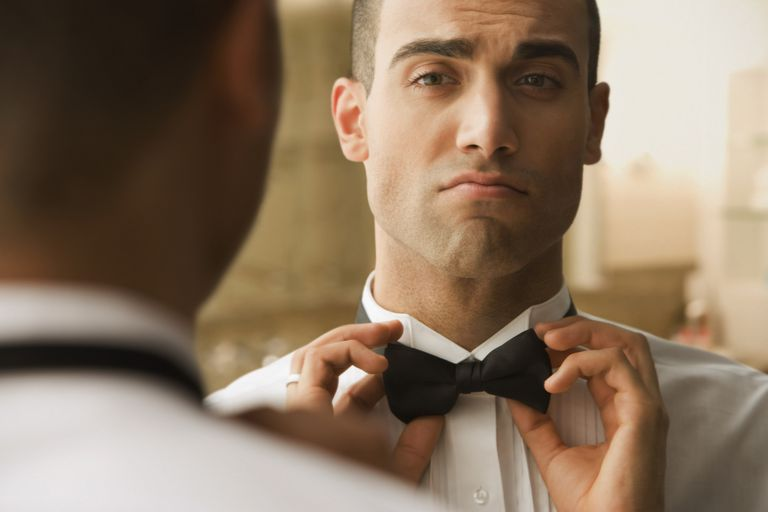 Man adjusts bow tie in mirror