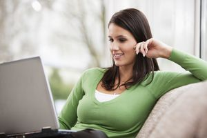 Young woman with laptop computer at home
