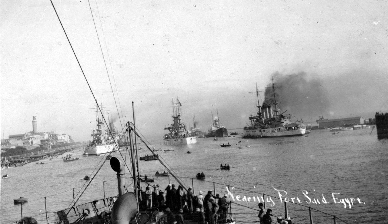 Three hite American battleships in a row steaming through the Suez Canal.