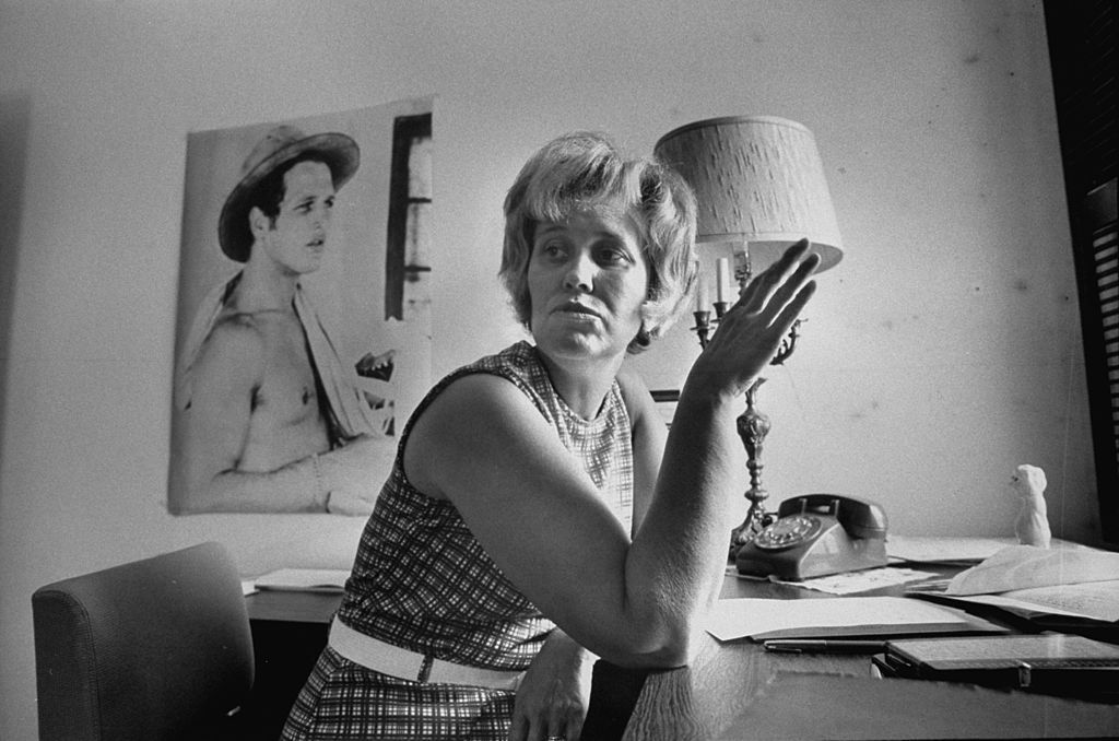 Erma Bombeck at home with rotary phone and portrait of Paul Newman on wall