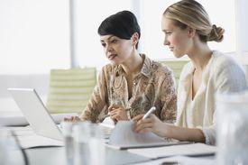 Businesswomen working on laptop together
