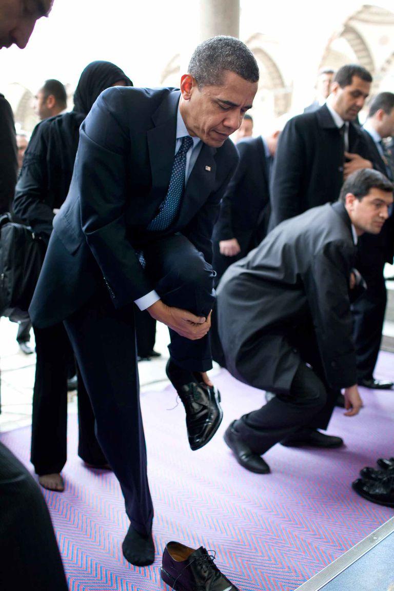 Former President Barack Obama removing his shoes