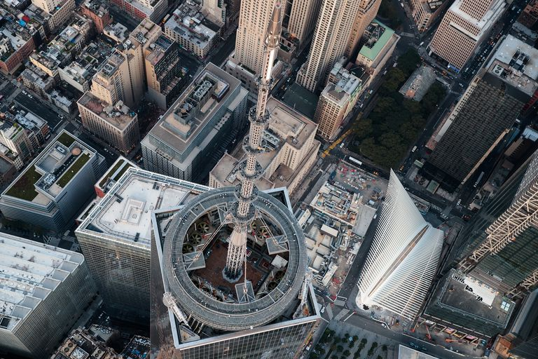 An aerial view of the top of One World Trade Center and its spire and the top of the white-spike transportation hub