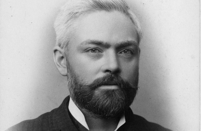 Black and white portrait of white man, receding grey hair, full dark beard, intense eyes