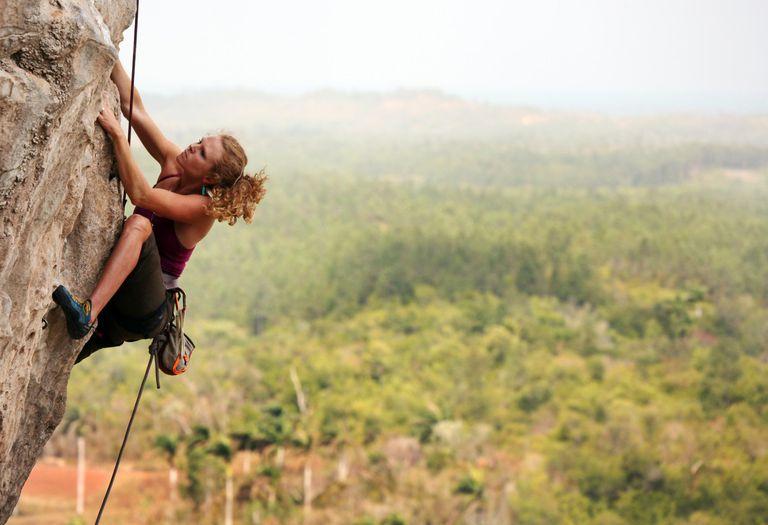 A woman rock climbing in Vinales, Cuba