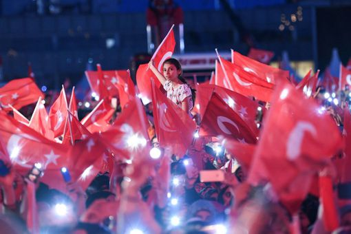 People wave Turkish national flags as they stand at the Ataturk International Airport in Istanbul on July 15, 2019. - Turkey commemorates, on July 15, 2019 the third anniversary of a coup attempt which was followed by a series of purges in the public sector and changes to boost Turkish President's powers.
