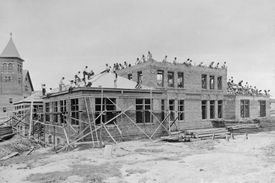 old black and white photo of many young people building a large building