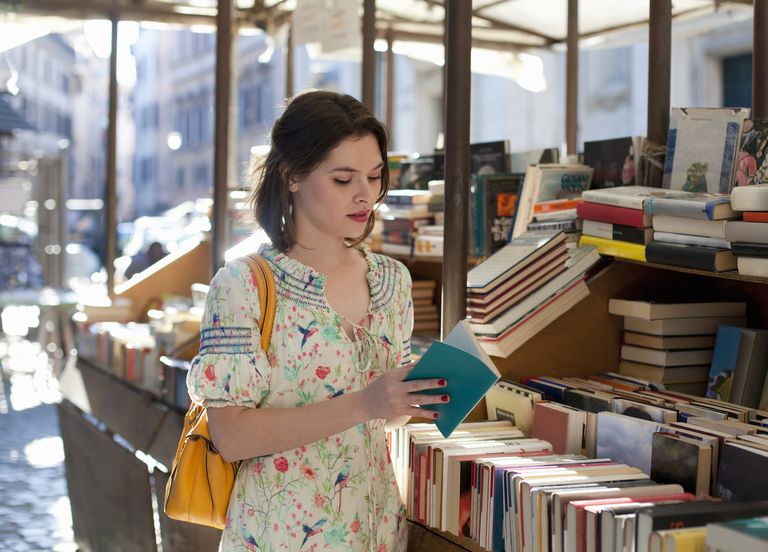 young woman flipping through book at bookstall