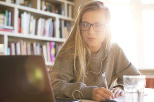 Teenage girl with headphones doing homework with laptop