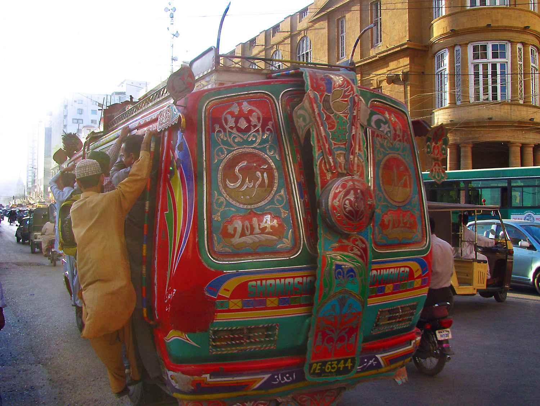An overloaded bus is running over the I. I. Chundrigar Road