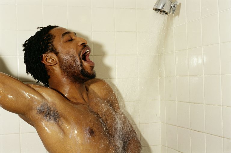 Young man singing in shower, eyes closed