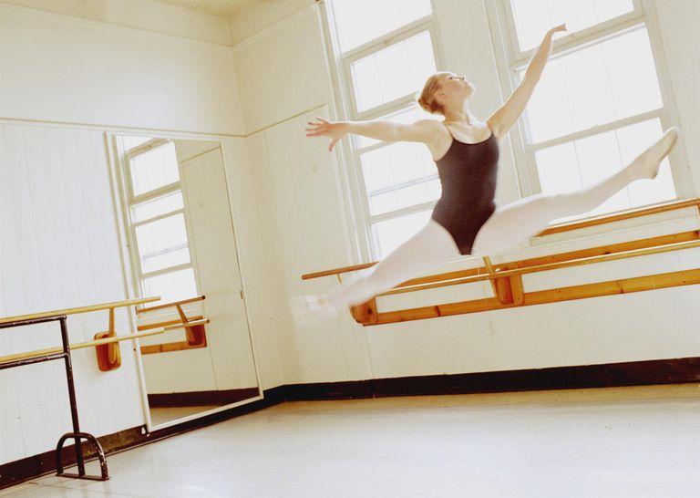 Ballet dancer (14-16) executing leap in dance studio (high key)