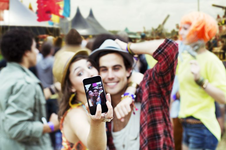 Couple taking self-portrait with camera phone at music festival