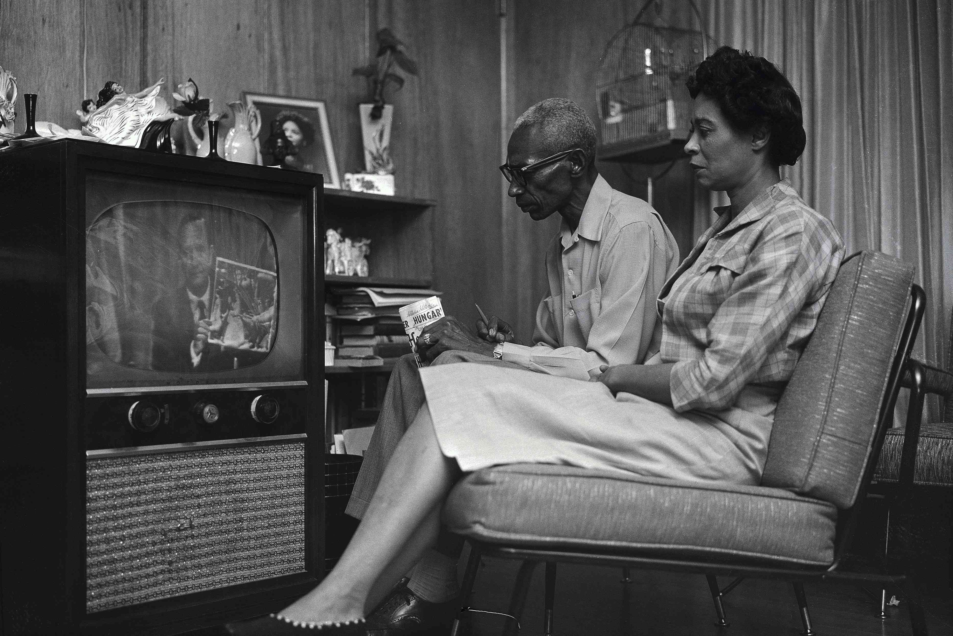 Daisy Bates and husband L.C. watching television with concerned looks on their faces