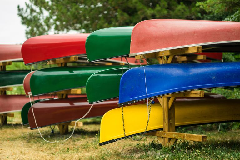 Colorful kayaks and canoes by the lake on a sunny day.
