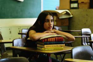 Student resting on books