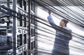 Woman working with carbon fiber thread on loom in carbon fiber production facility