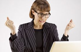 VERY ANGRY AND FRUSTRATED BUSINESS WOMAN ON LAPTOP