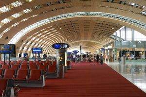 airport terminal with red carpeting and seats below a curved ceiling of lattice wood