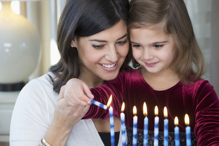 Mother and daughter lighting Hanukkah menorah