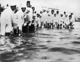 Followers of Gandhi fill plastic bottles with seawater during the Salt March of 1930 in India, to protest British colonial salt taxes.