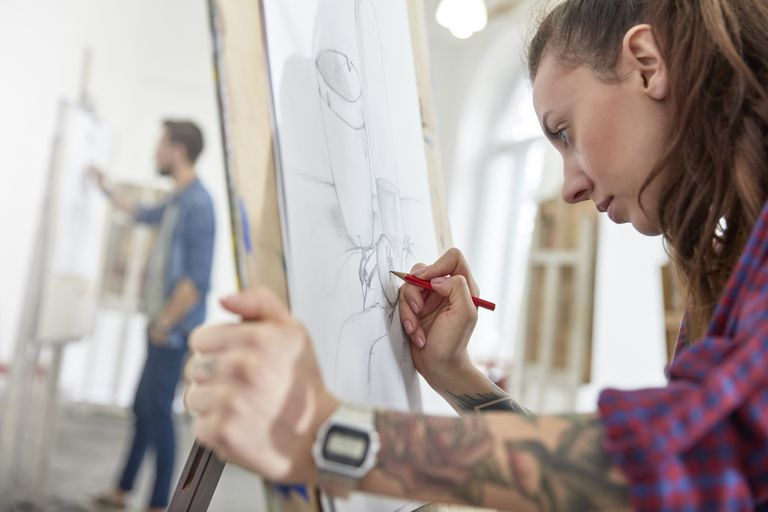 Focused female artist with tattoo sketching at easel in art class studio