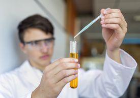School student dripping liquid into test tube