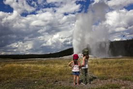 Two young girls watch as Old Faithful is Erupting