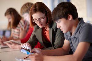 A teacher helping a student on an ipad.