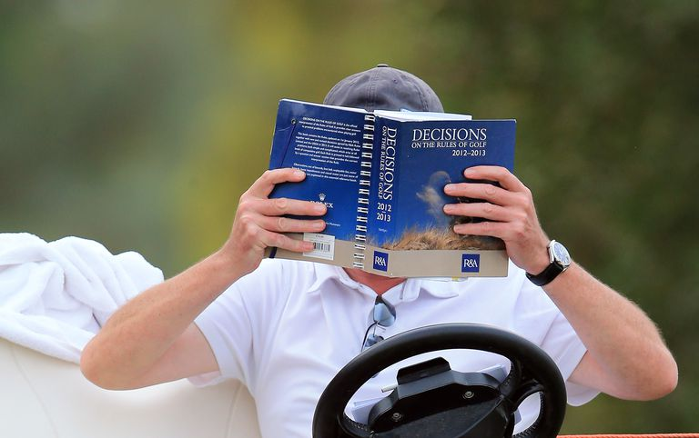 Rules official consults the golf rule book