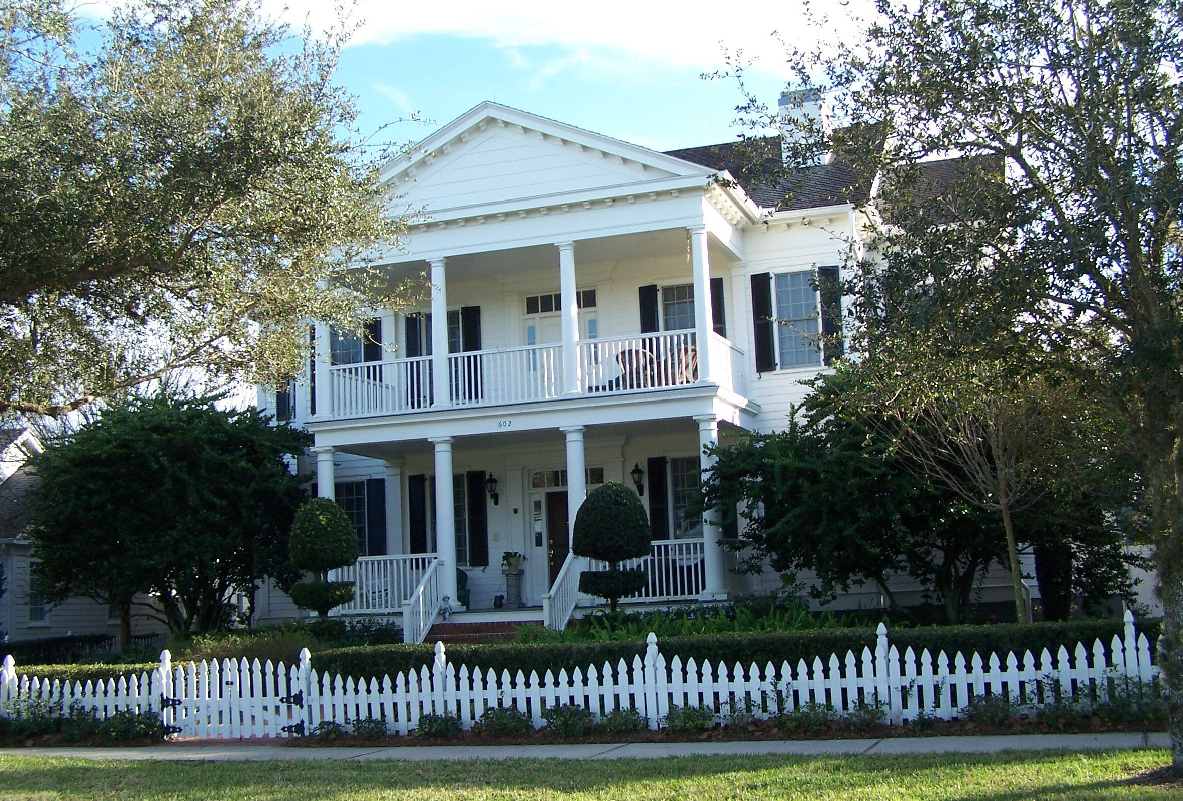 Overly small picket fence in front of a massive two-story classical estate