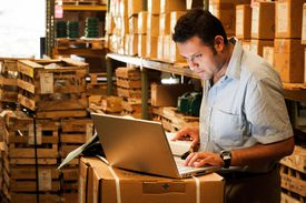 Working performing warehouse calculation on laptop.