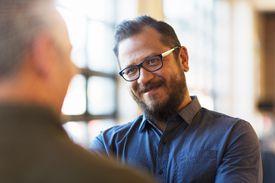 Man smiling at his conversation partner