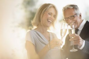 Smiling older couple toasting with champagne.