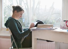 Sixteen year old girl studying and writing notes next to window