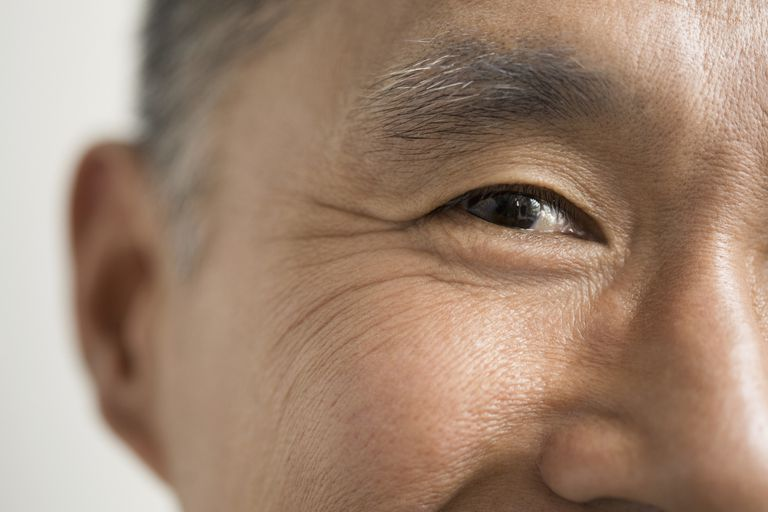 An extreme close up of a smiling man's eye