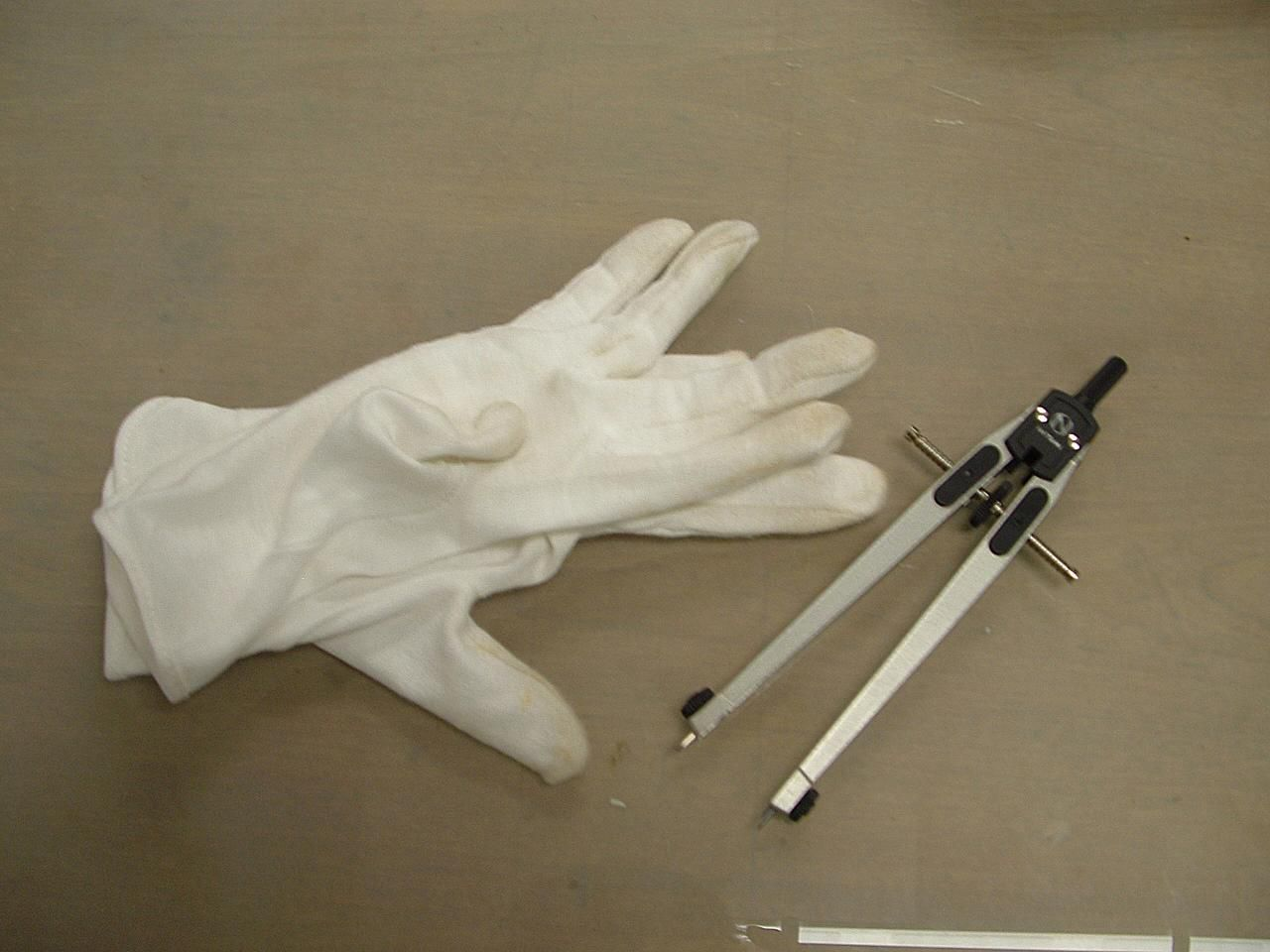 Calipers and cotton gloves are used during the analysis of artifacts.