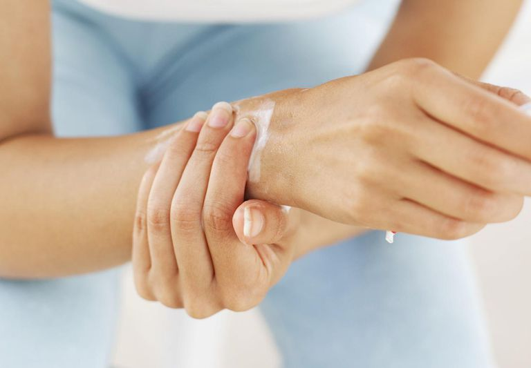 Close-up of a woman applying an anti-inflammatory cream to her wrist