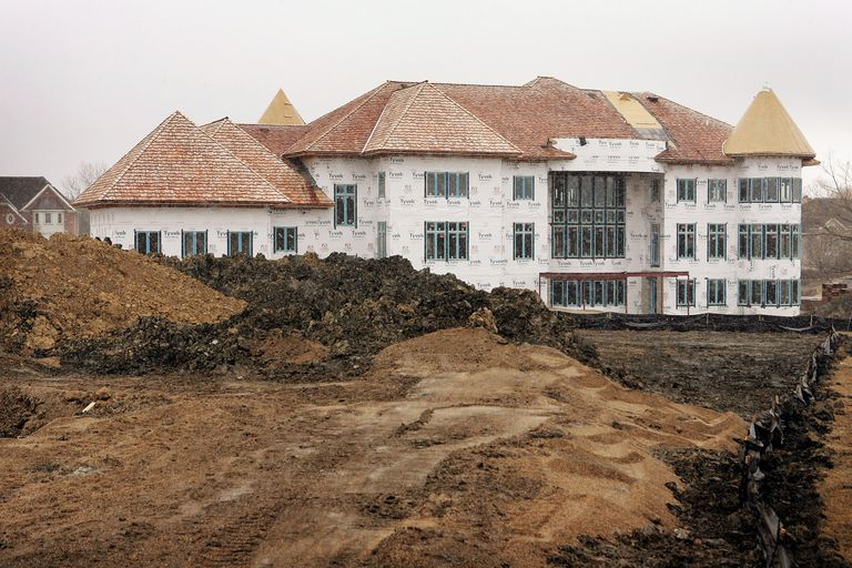 overly large house with multiple roof types under construction