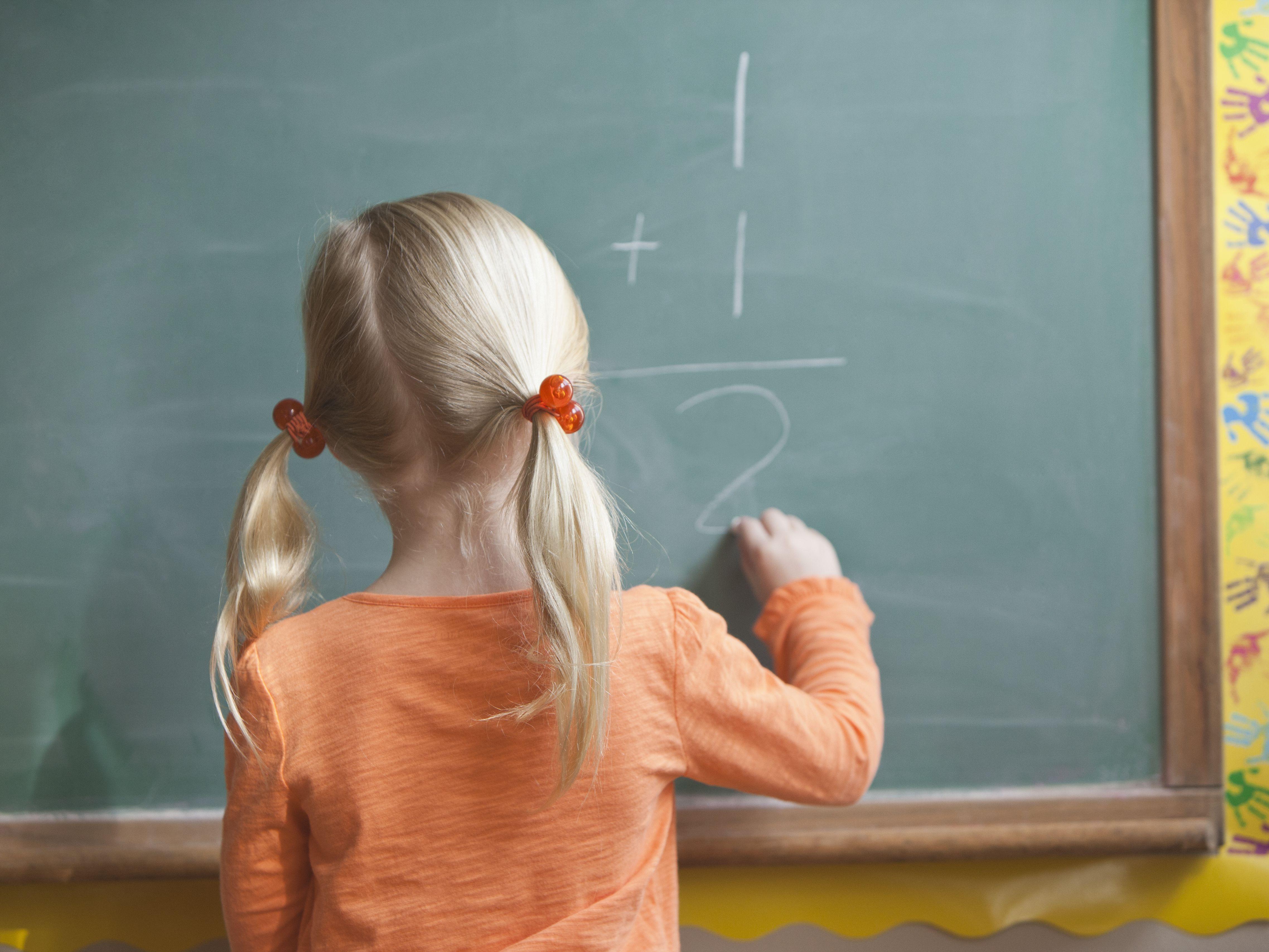 caucasian girl solving math problem on blackboard dcd5f9b c1d8b