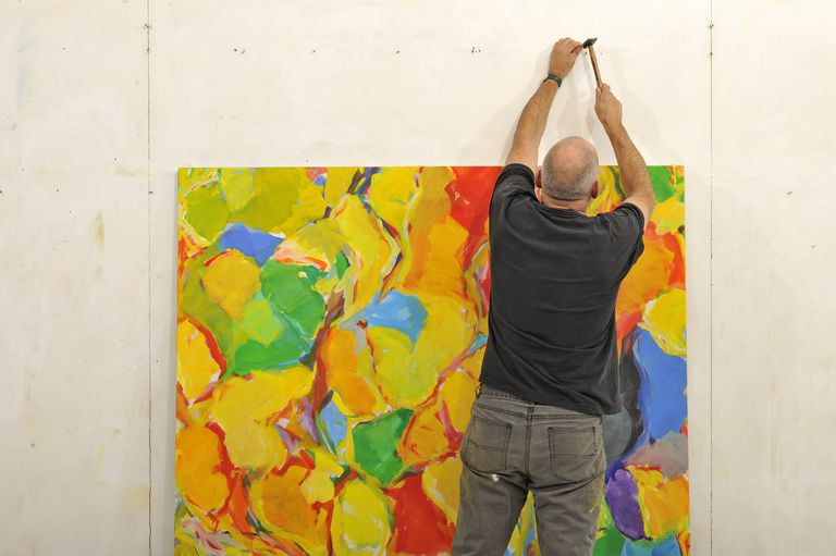 Painter hanging his art on a wall