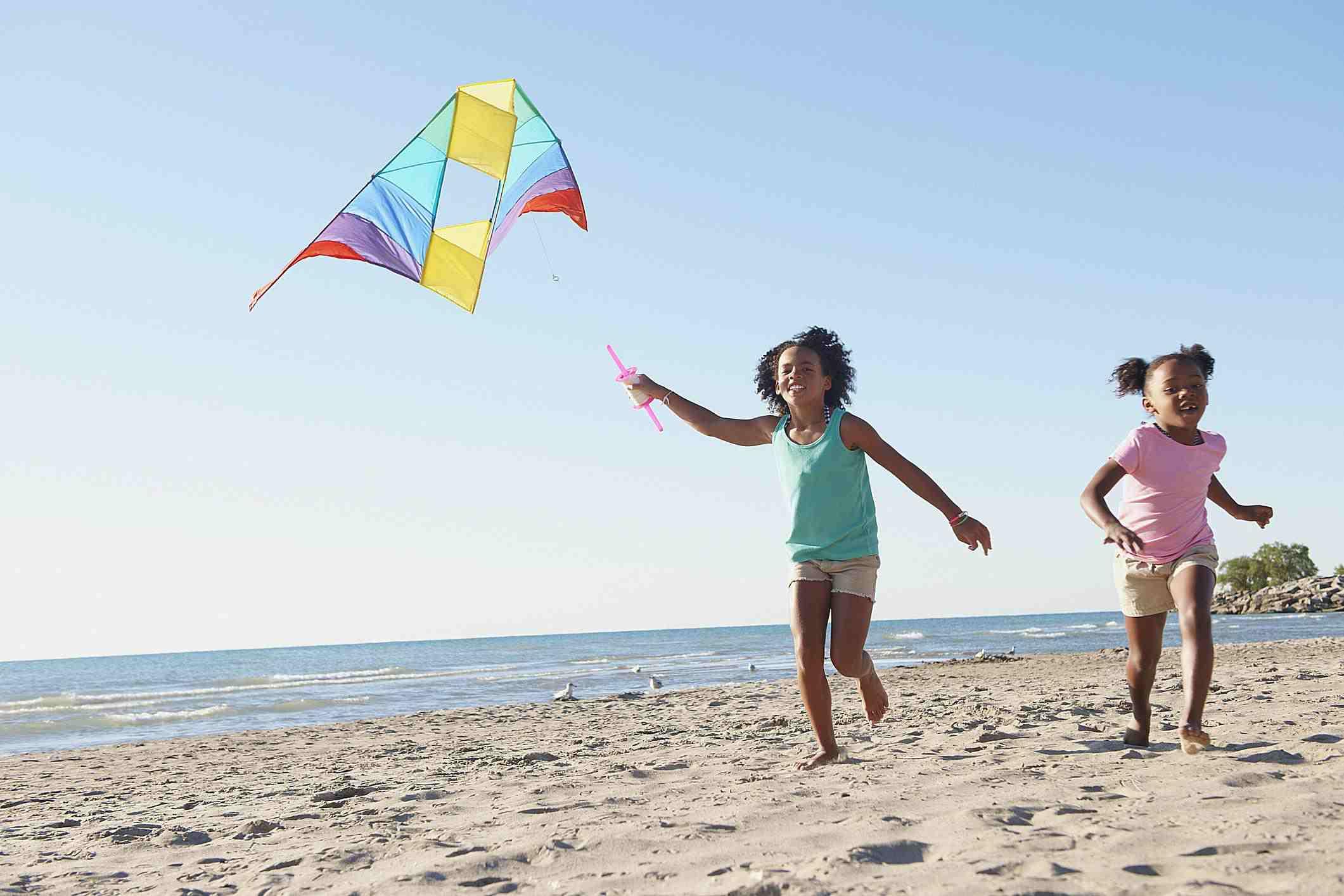 Girls flying kites on beach