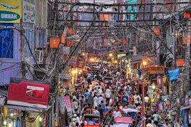 Street view of Delhi, India teeming with people.
