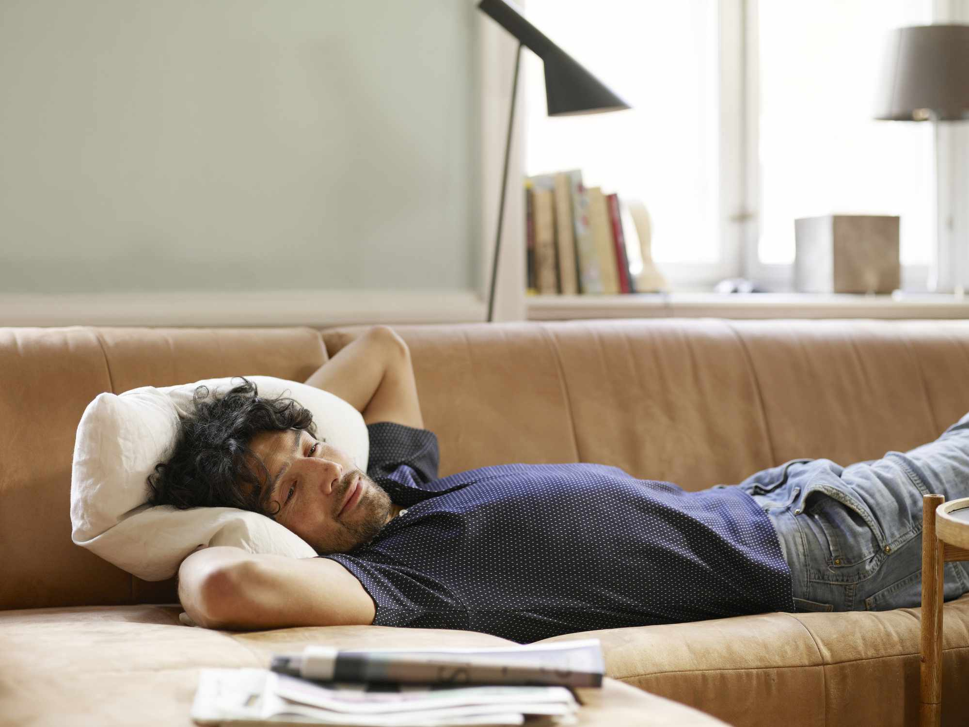 Guy lying on the couch, watching tv