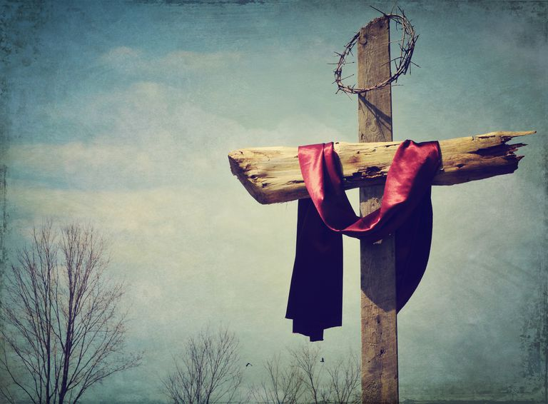 A red sash and crown of thorns hanging from theChristian Cross