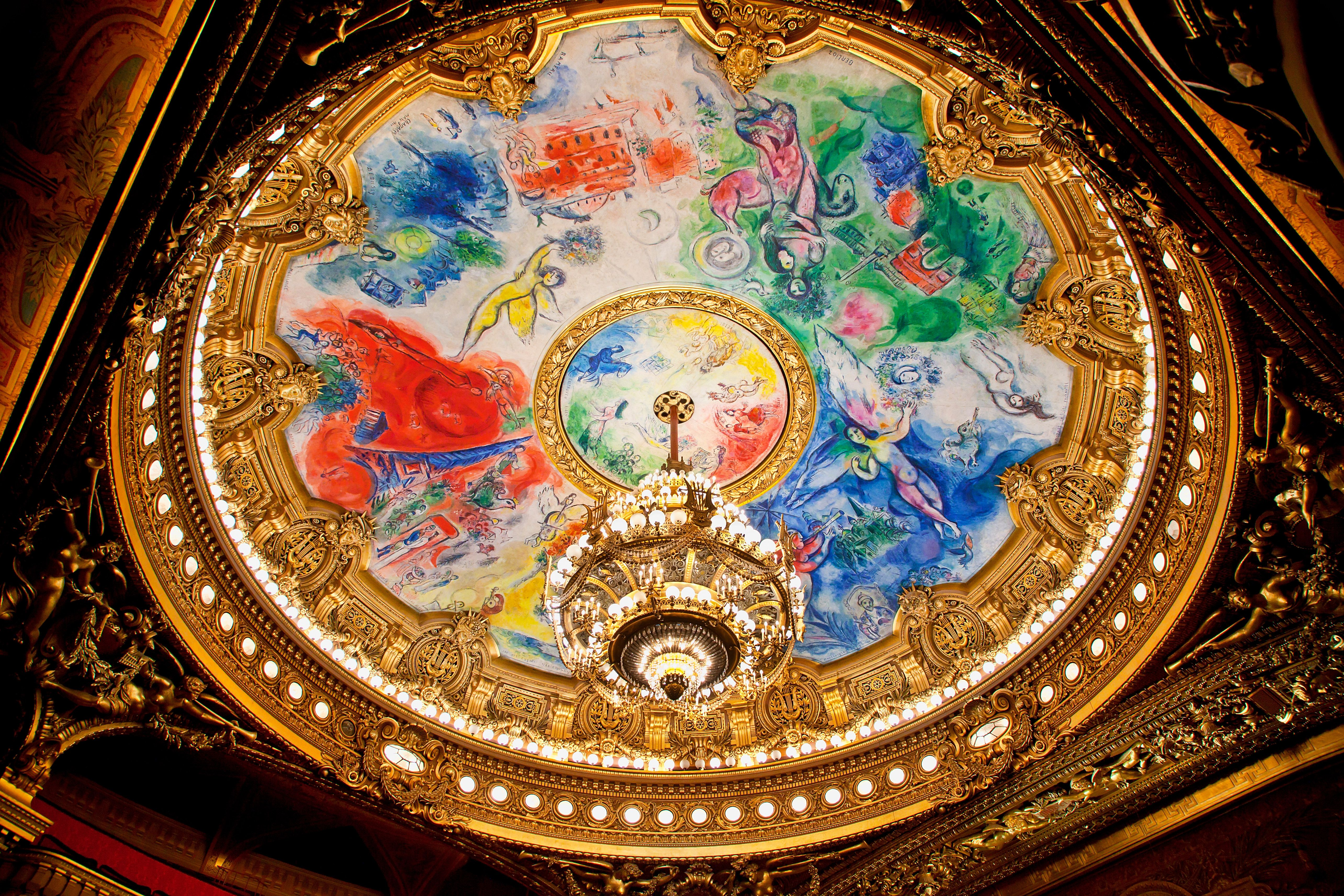 Round ceiling with paintings of colorful flying figures surrounded by gold molding