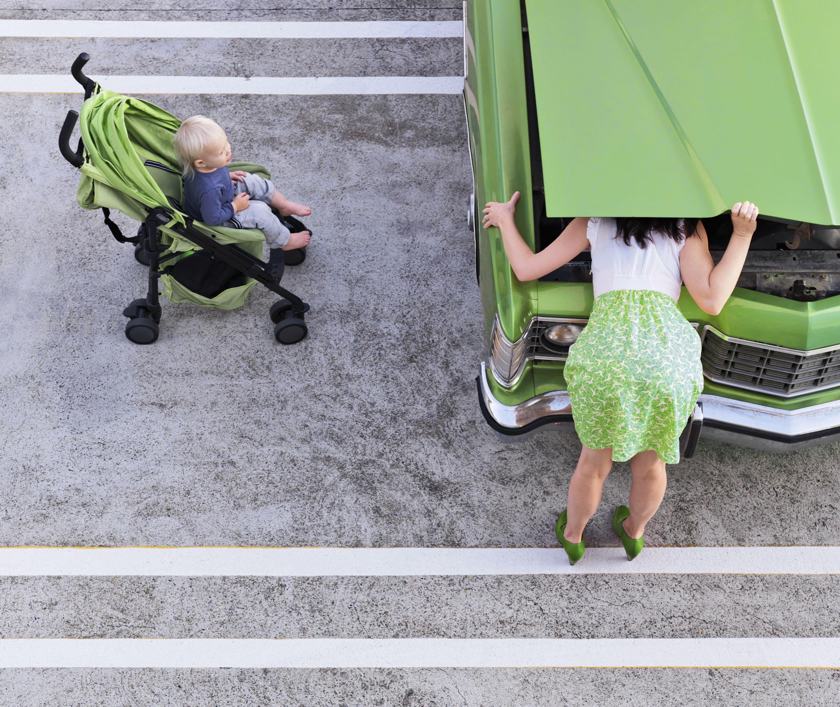 Γιος βλέποντας τη μητέρα που ελέγχει τη μηχανή του κλασικού αυτοκινήτου