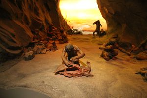 Paleolithic exhibit showing early humans living in a cave.