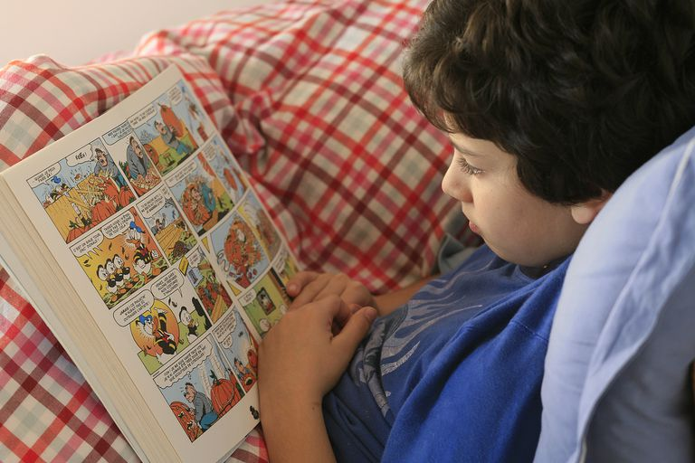 Boy Reading Comics in Bed