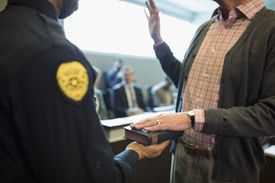 Male bailiff holding bible for witness in legal trial courtroom